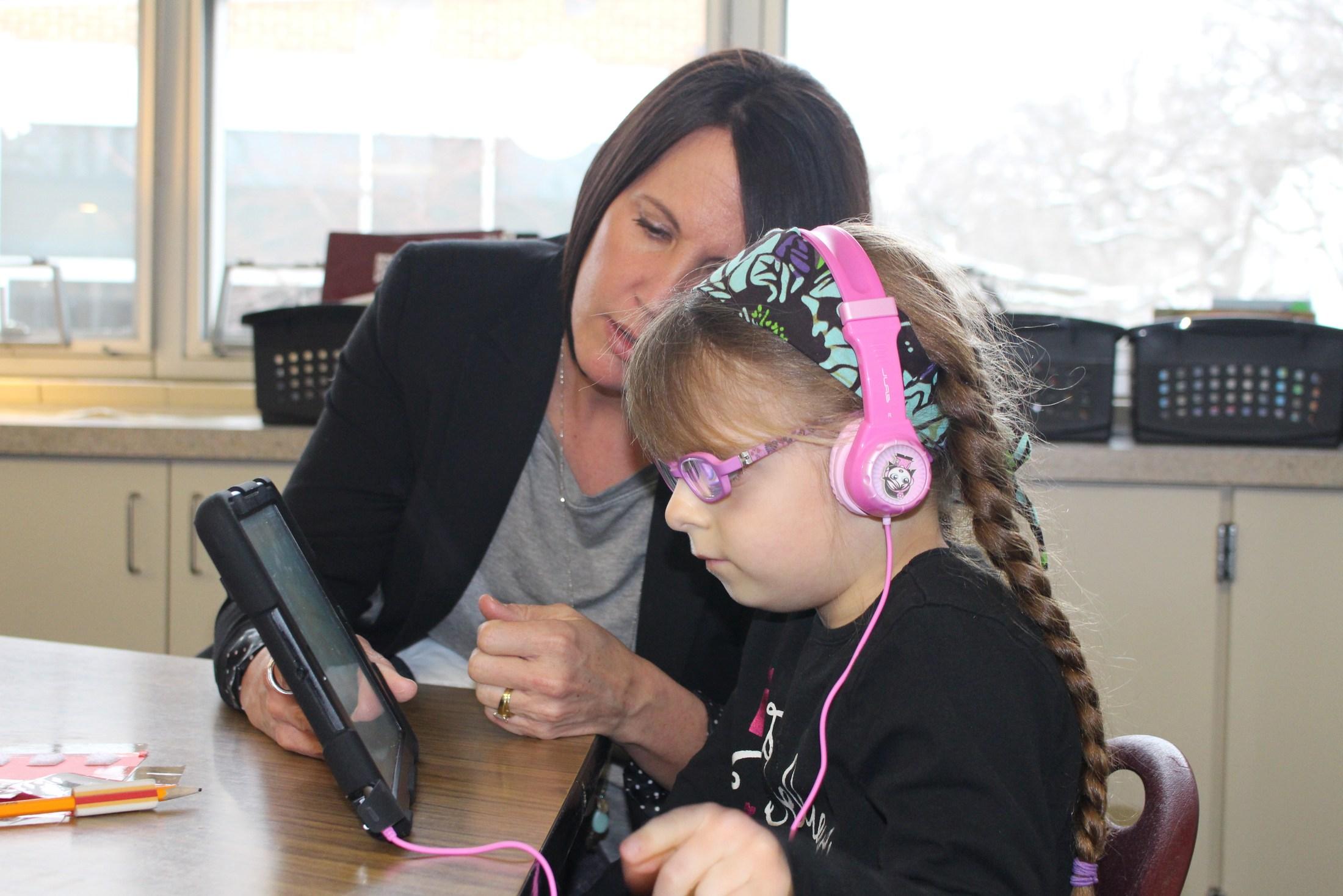 teacher with girl on ipad