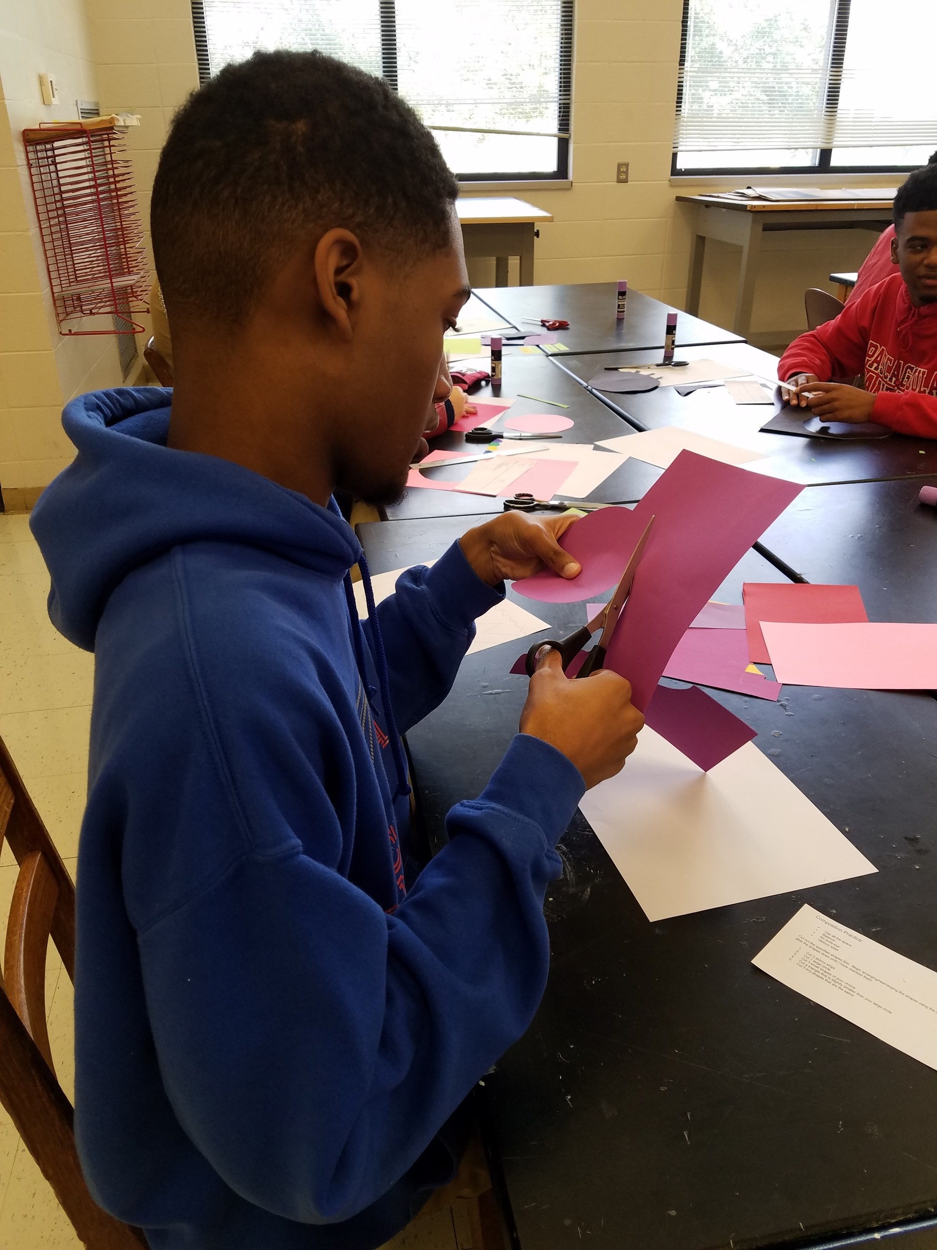 Student cuts shapes out of colored paper