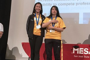 two students on stage with medals