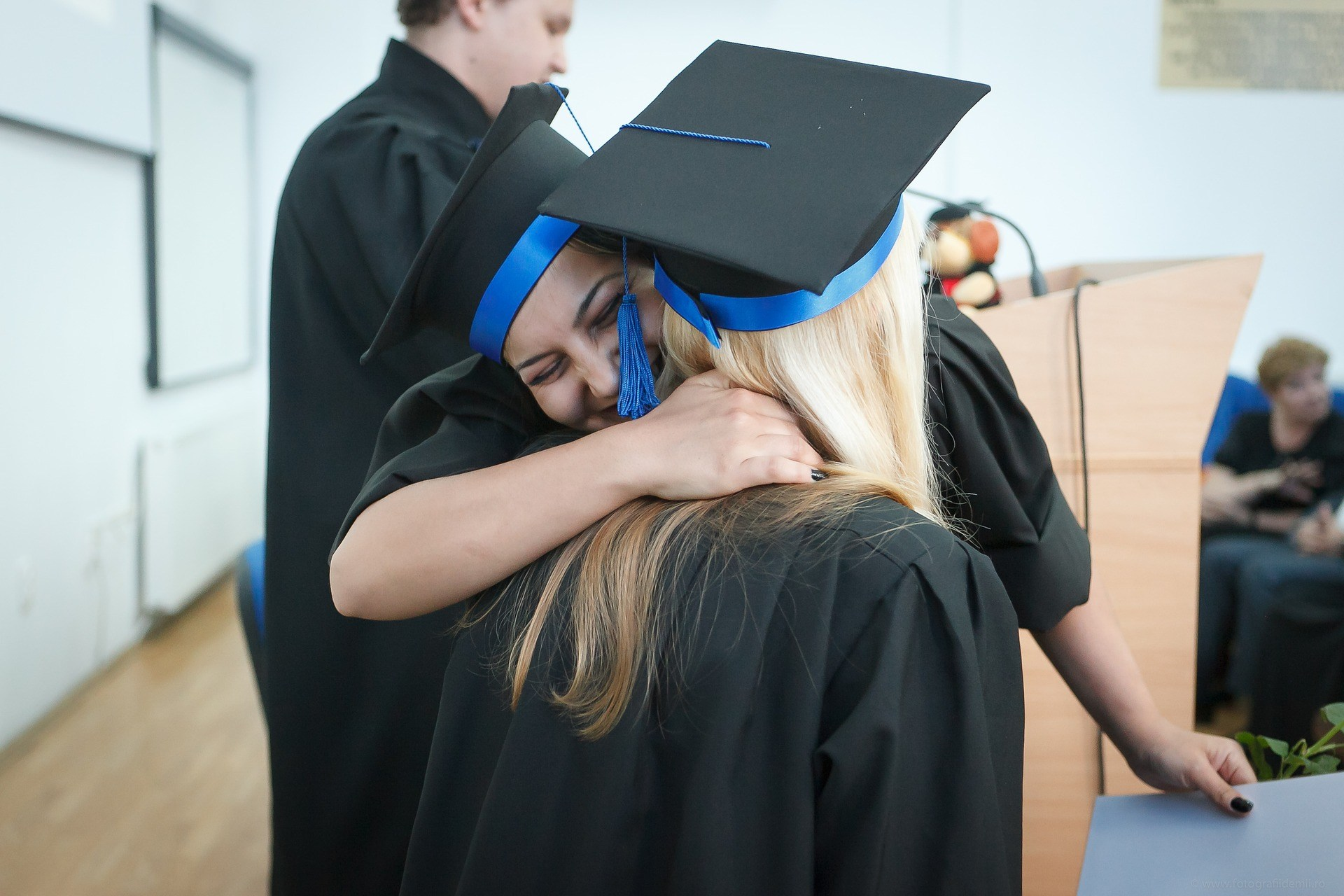 two high school graduate girls hugging