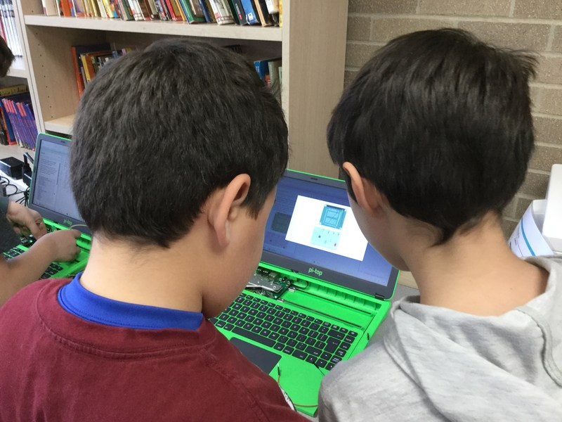 2 male students interacting with a green pi-top computer.