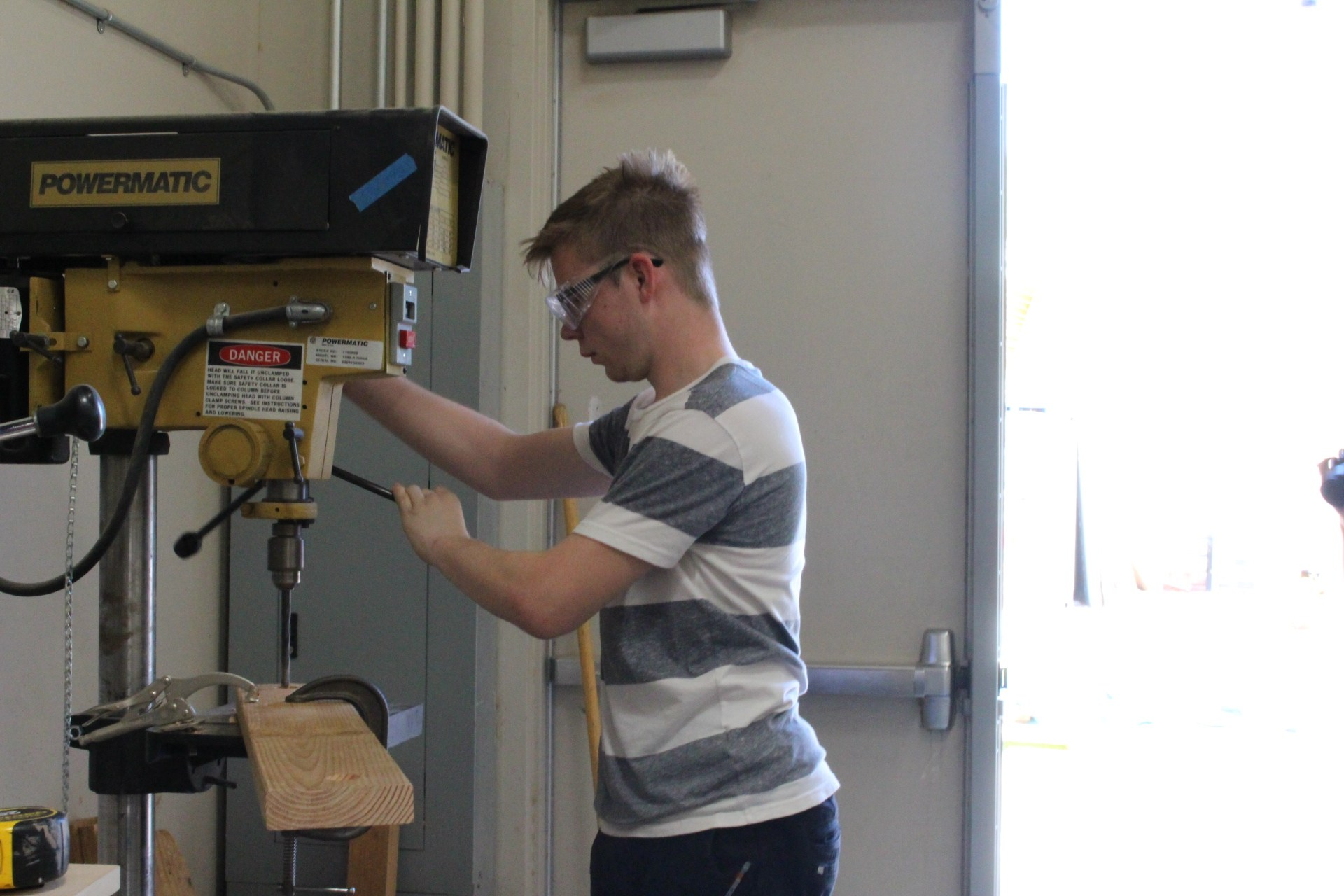 A student using the drill press