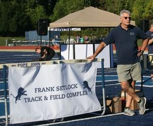 Frank Setlock poses next to sign