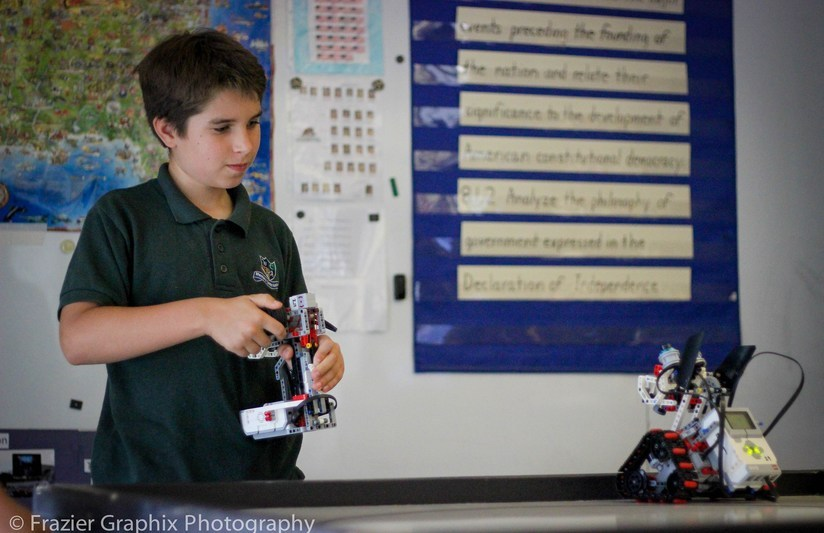 Student holding a robot