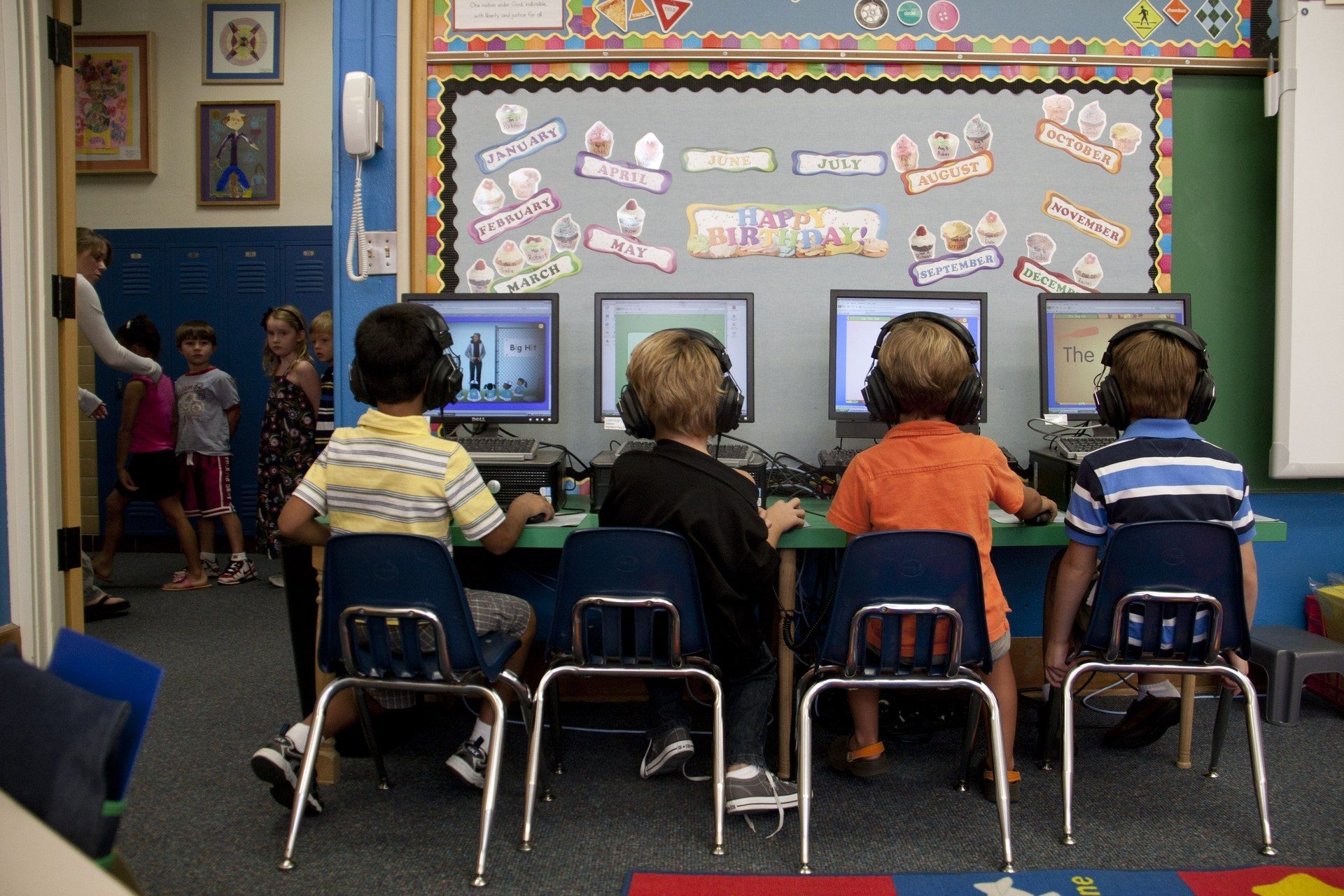 Four students enjoy using the classroom computers and headsets for learning activities