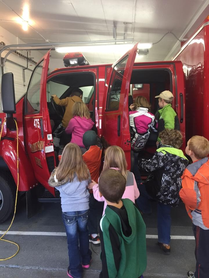 Students climbing into fire truck.