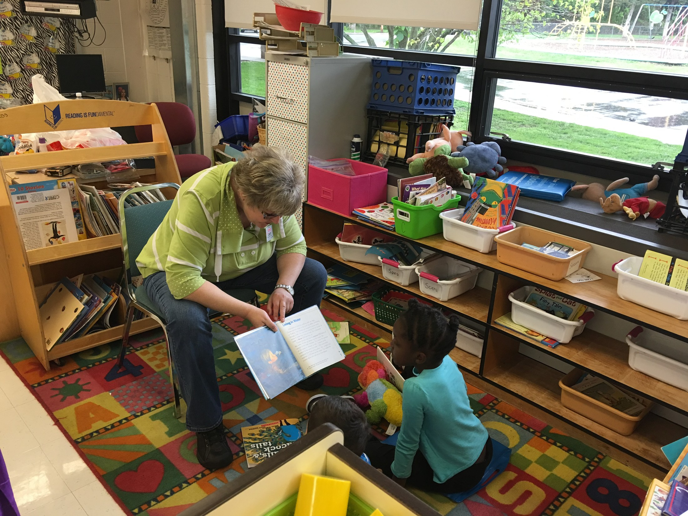 Costco employee reading as a Reader Leader to a Butcher-Greene student