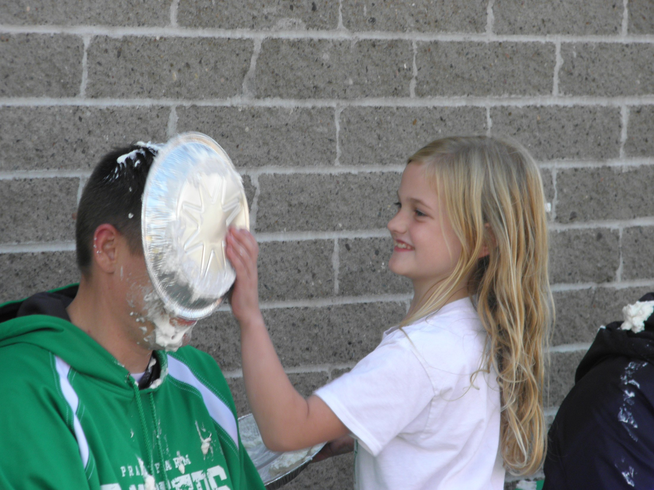 Student holding pie pan against principal's face.