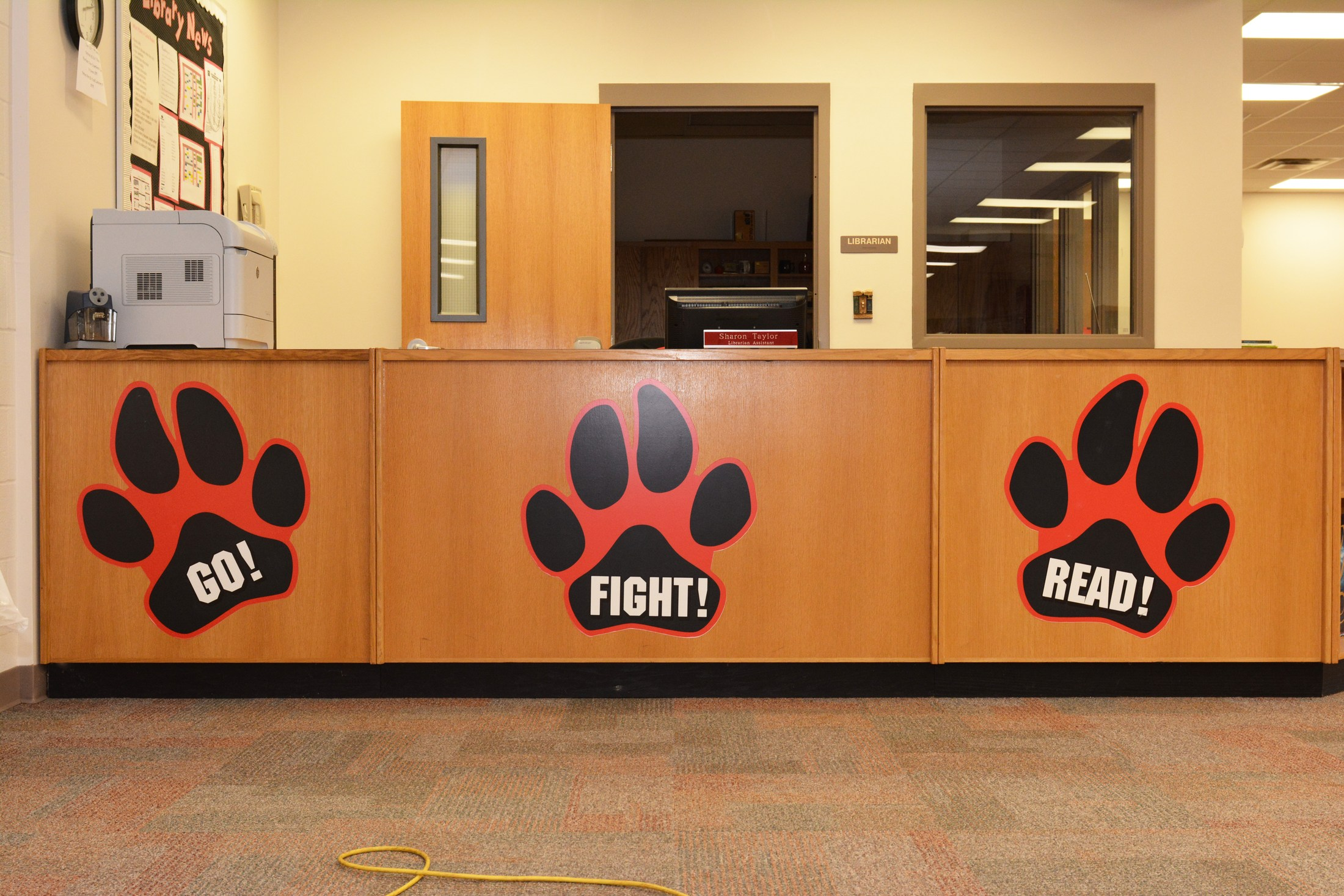 HS library circulation desk with Go! Fight! Read! paw prints.