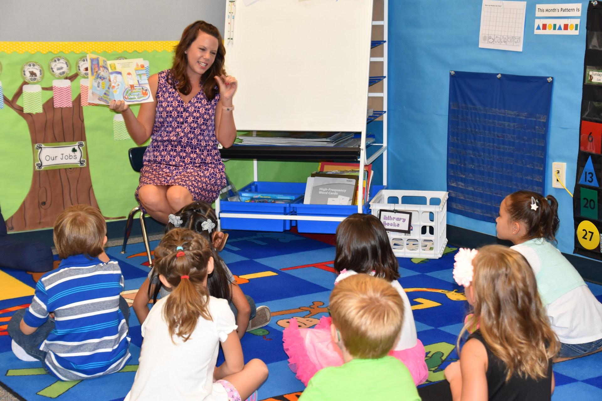 Kindergarten students at orientation reading with teacher