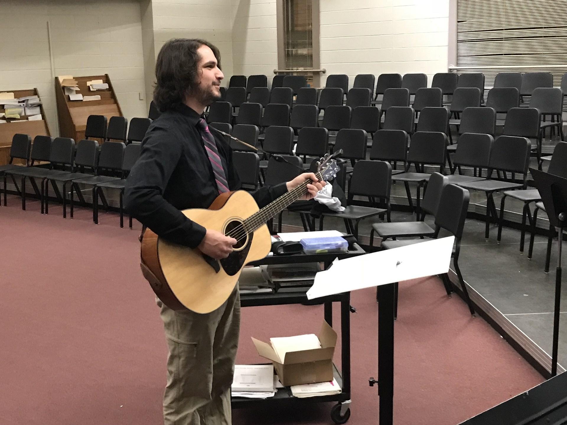 Teacher playing guitar in class