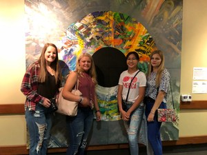 High school students pose next to one of the paintings at ArtPrize.