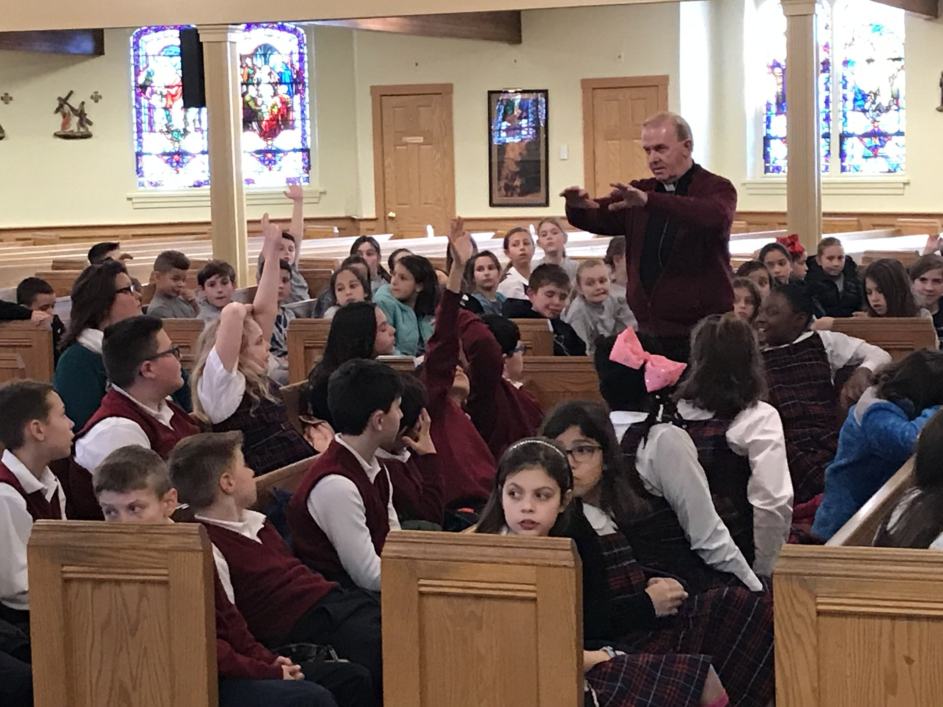 Priest explaining answer to fourth-grade students during retreat