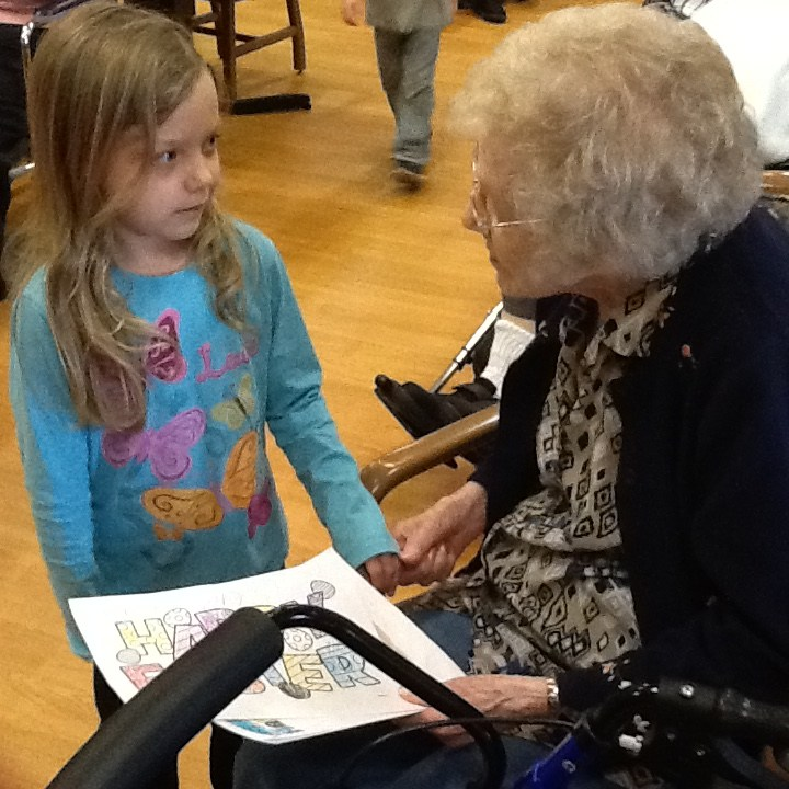 Elderly visiting with students.