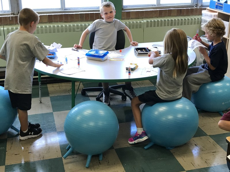 Kids sitting around a table on yoga balls