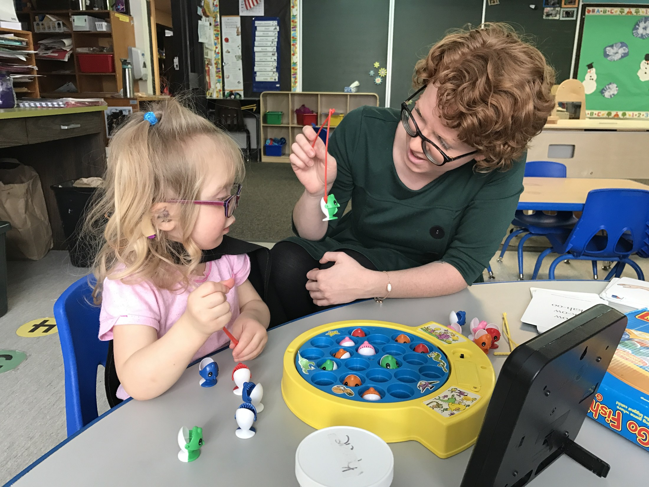 A speech language pathologist works one on one with a student.