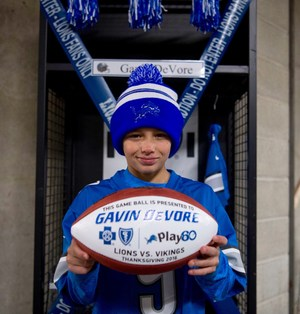 TKMS student Gavin DeVore holds his Detroit Lions game ball after his VIP day at the Thanksgiving parade and game.