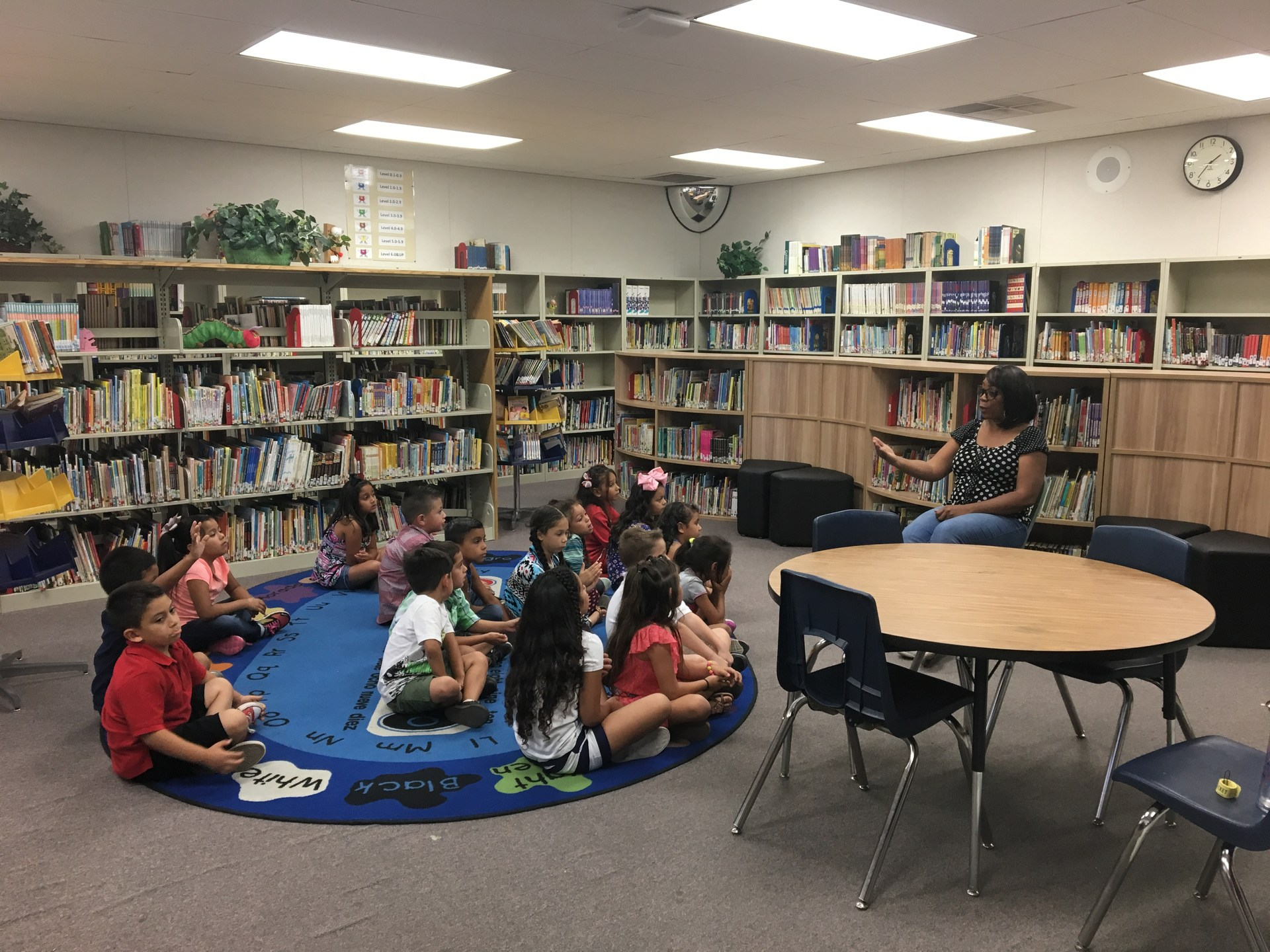 librarian working with a class at the carpet in the library