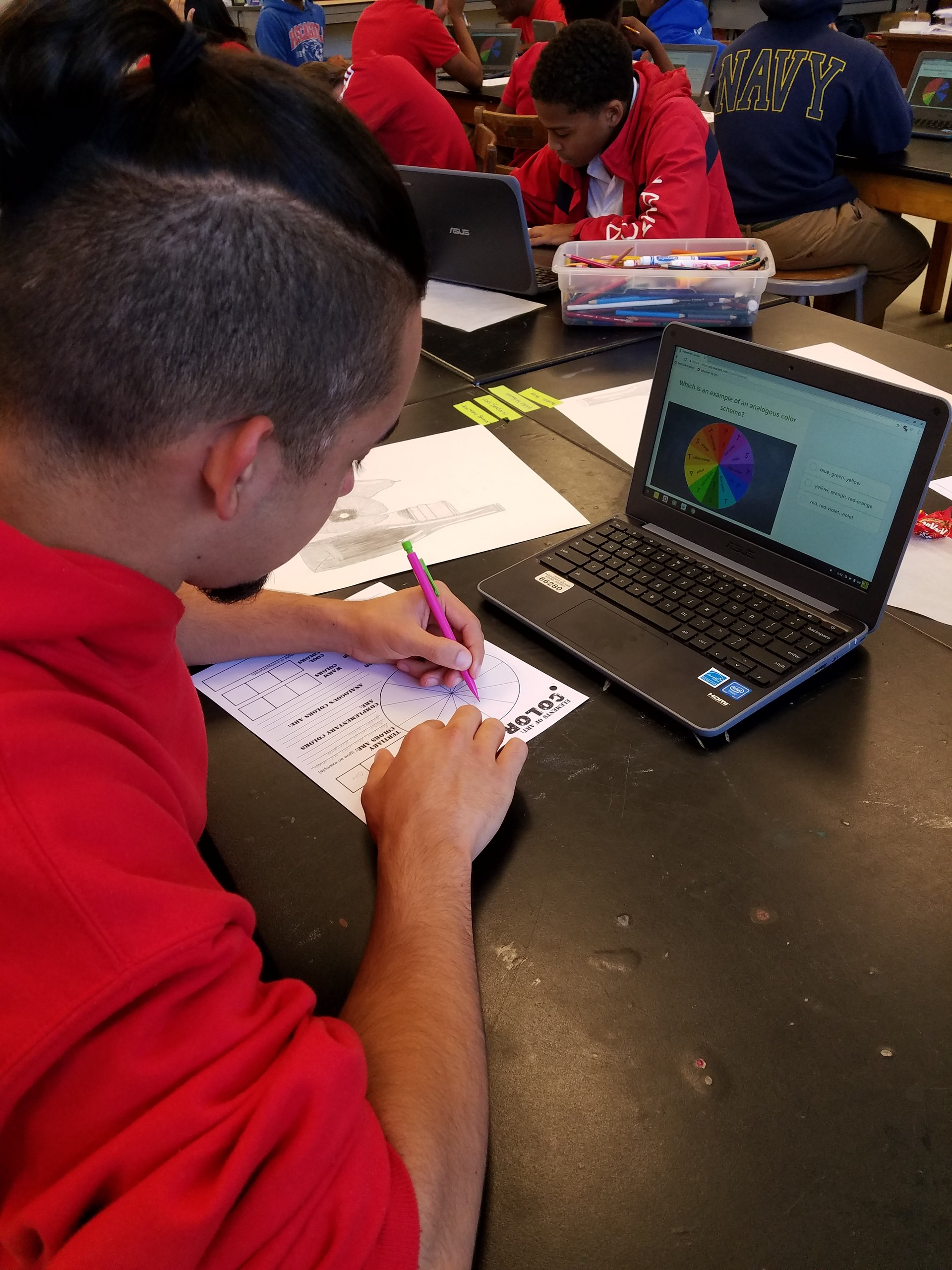 Student is using a chromebook to take notes on color