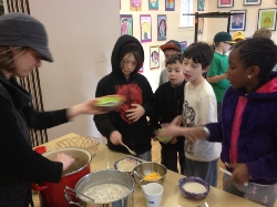 A woman serves soup to a group of children