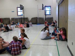 Fifth grade students work in groups in the gym.