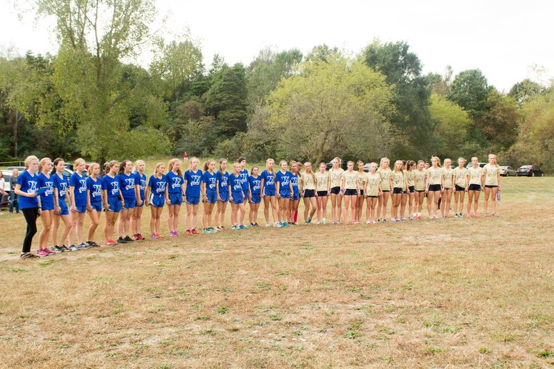 Girls from both teams stand in a line holding hands for a short tribute to Delaney Bush before the meet.