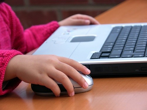 Young child sitting at desk with laptop.