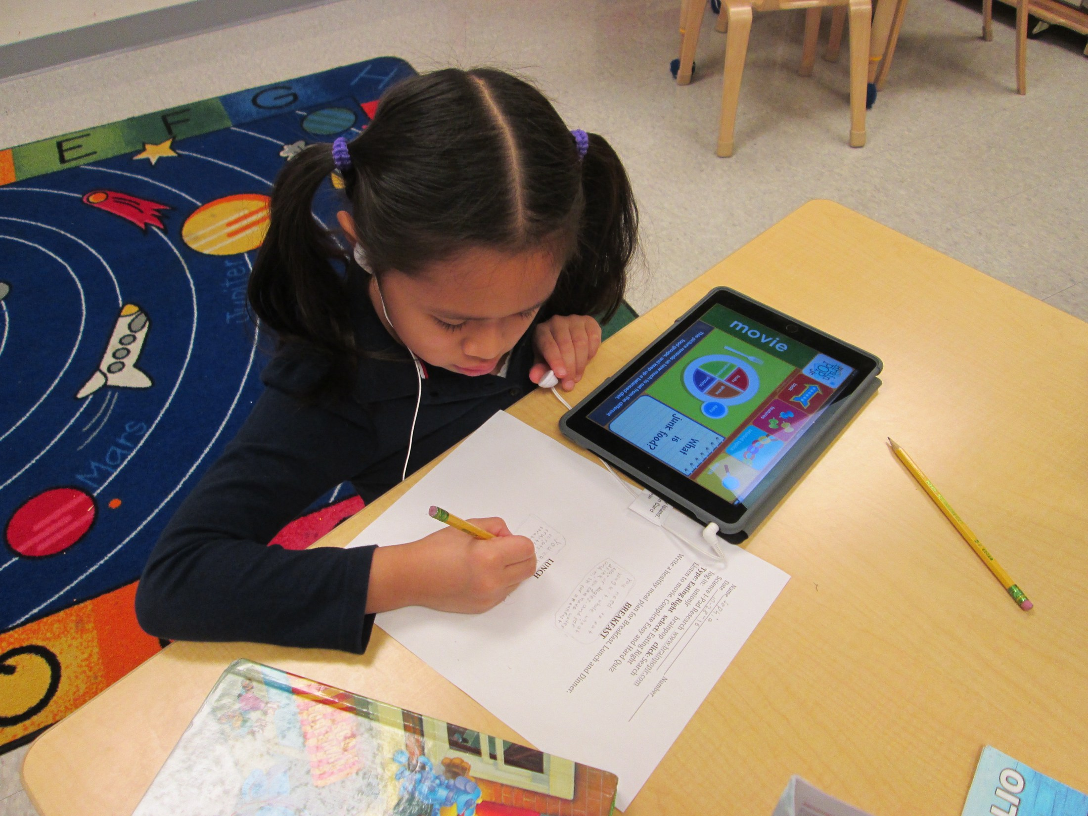 girl working with ipad and activity sheet