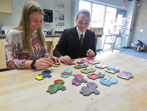 TKHS students Monica Bluhm and Samantha Craven look over their wooden puzzles they've made.
