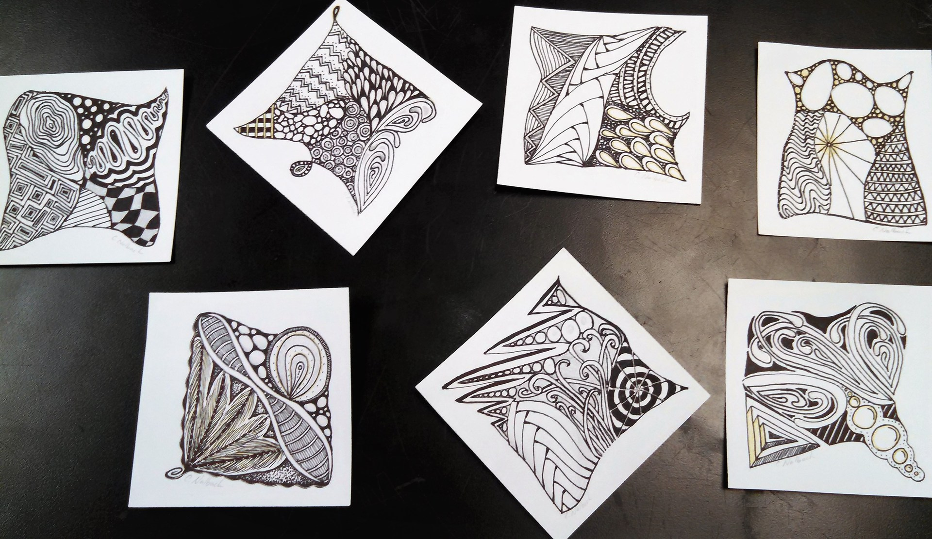 7 squares of paper with zentangle patterns drawn on them