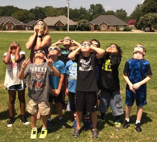Students and teacher watching solar eclipse