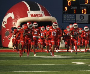MHS Football players running on to the field.
