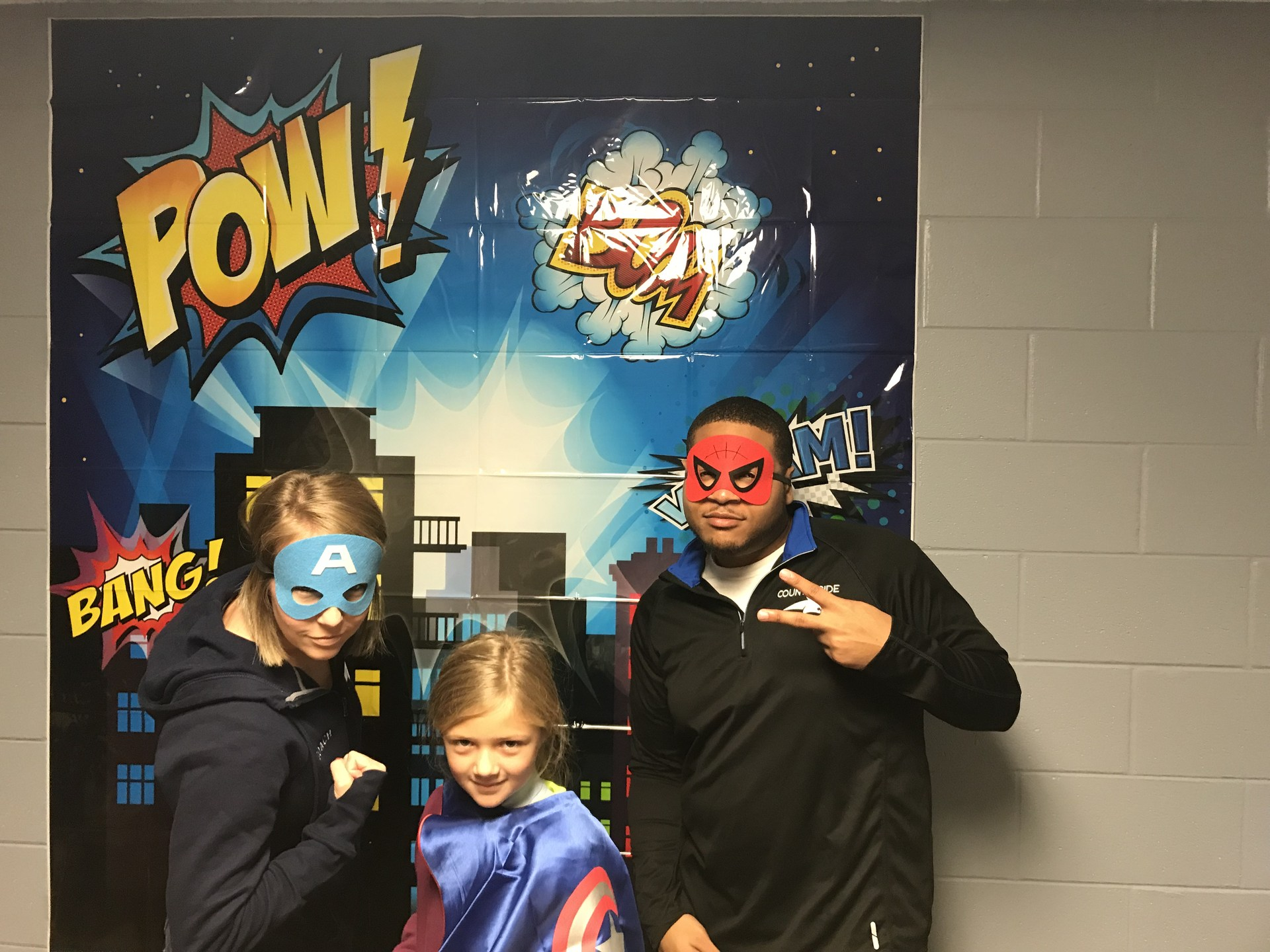 Mrs. Furney, student, and Mr. Smith posing for the Year-O of the Super Hero