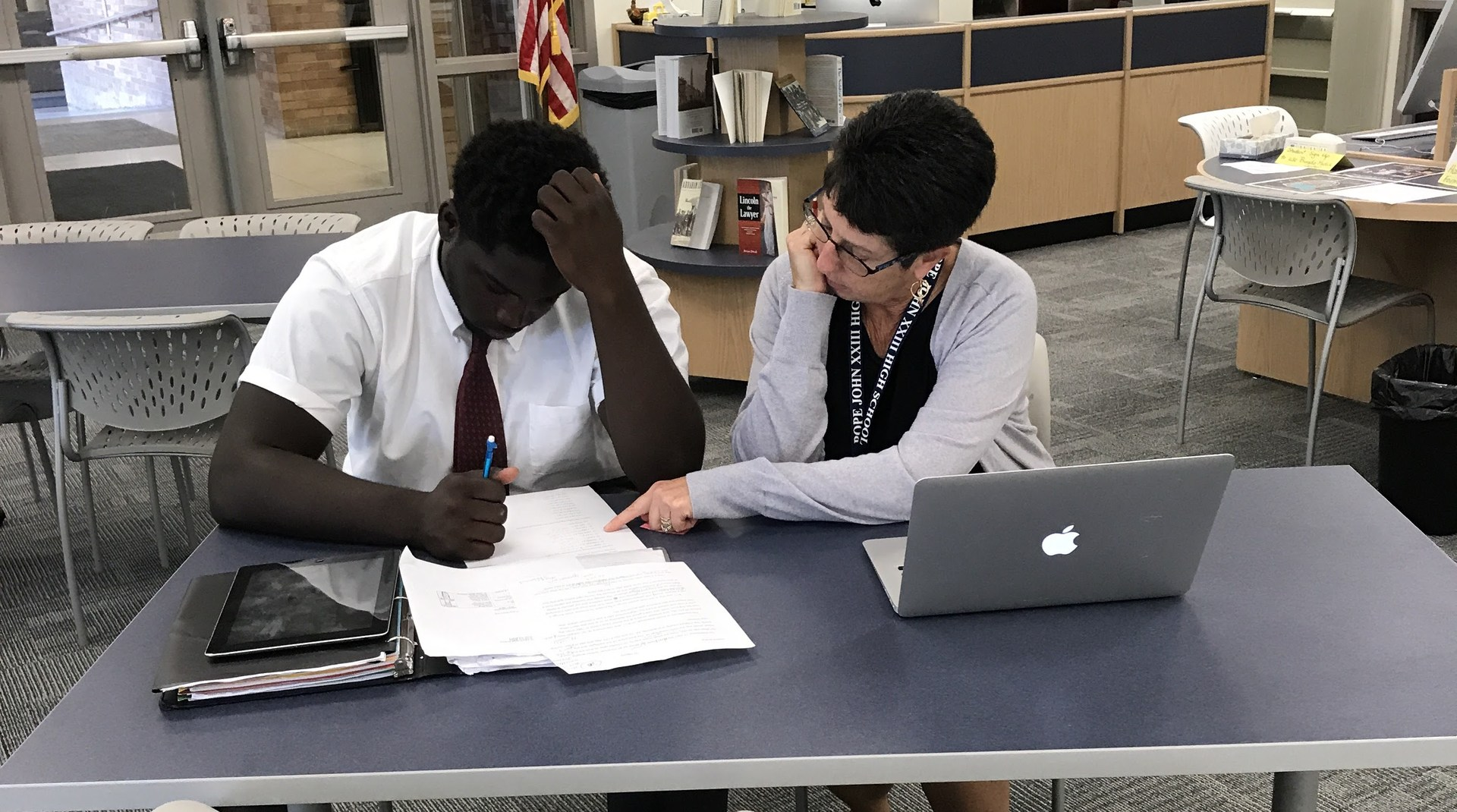 Media specialist helping student