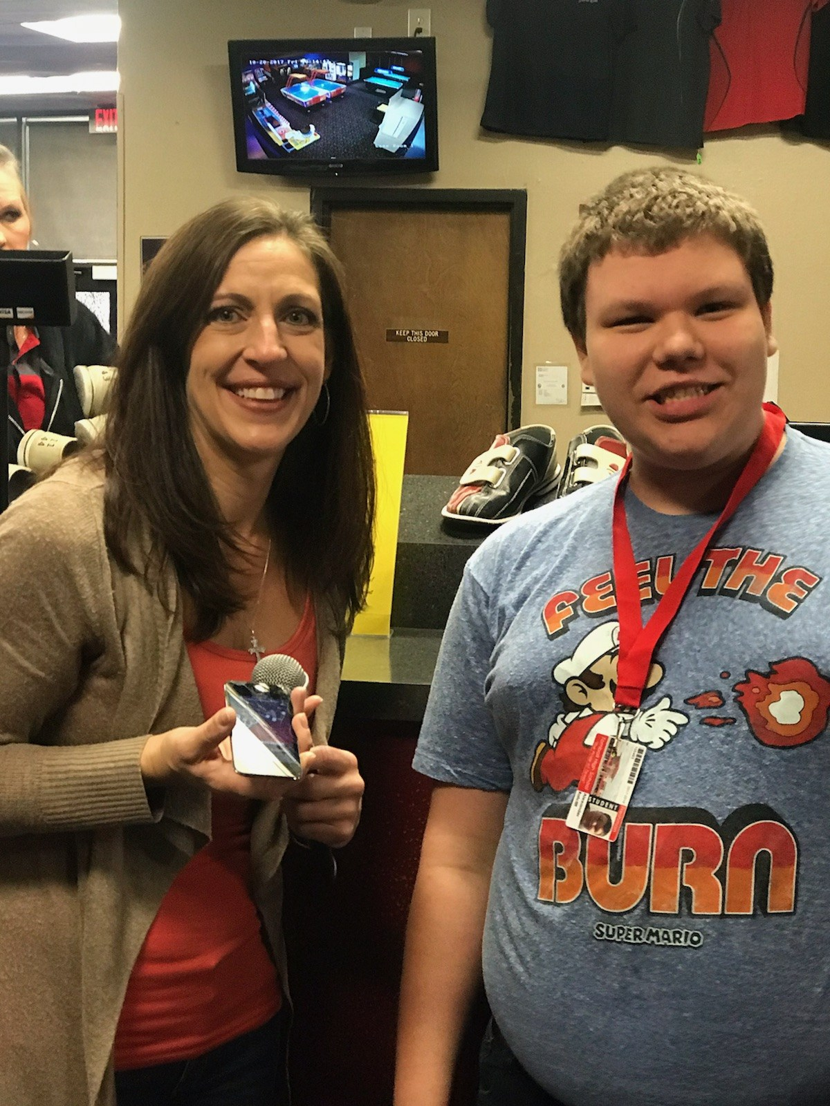 Student Support Employee standing with student with a medal from Bowling Challenge Day
