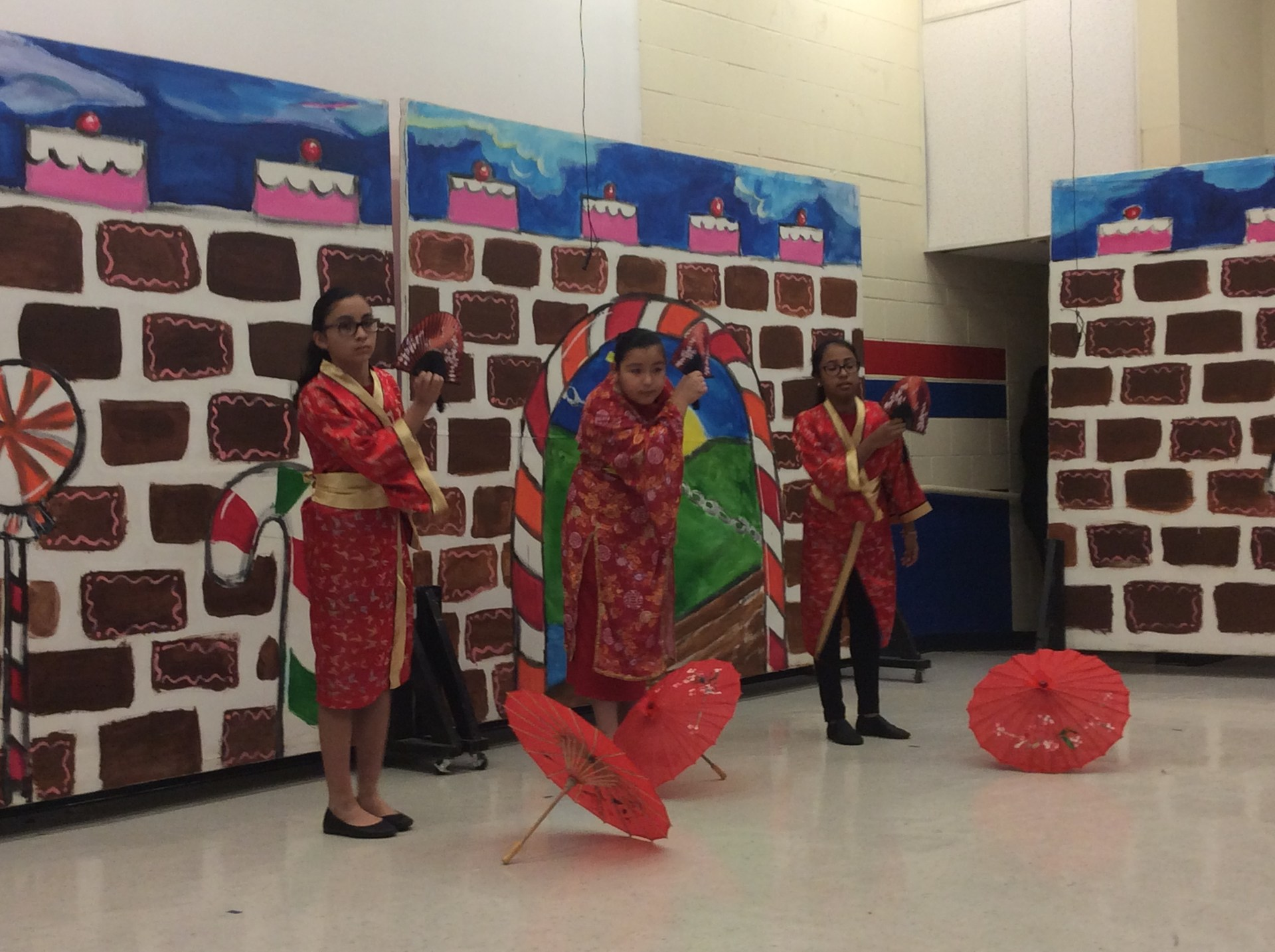 Asian dancers with umbrellas on stage.