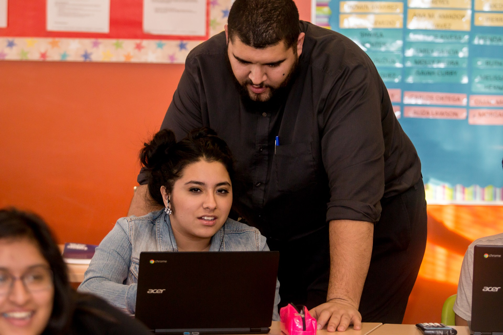 Student and teacher working on computer