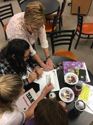 Teachers pointing at a worksheet and talking about possible solutions.