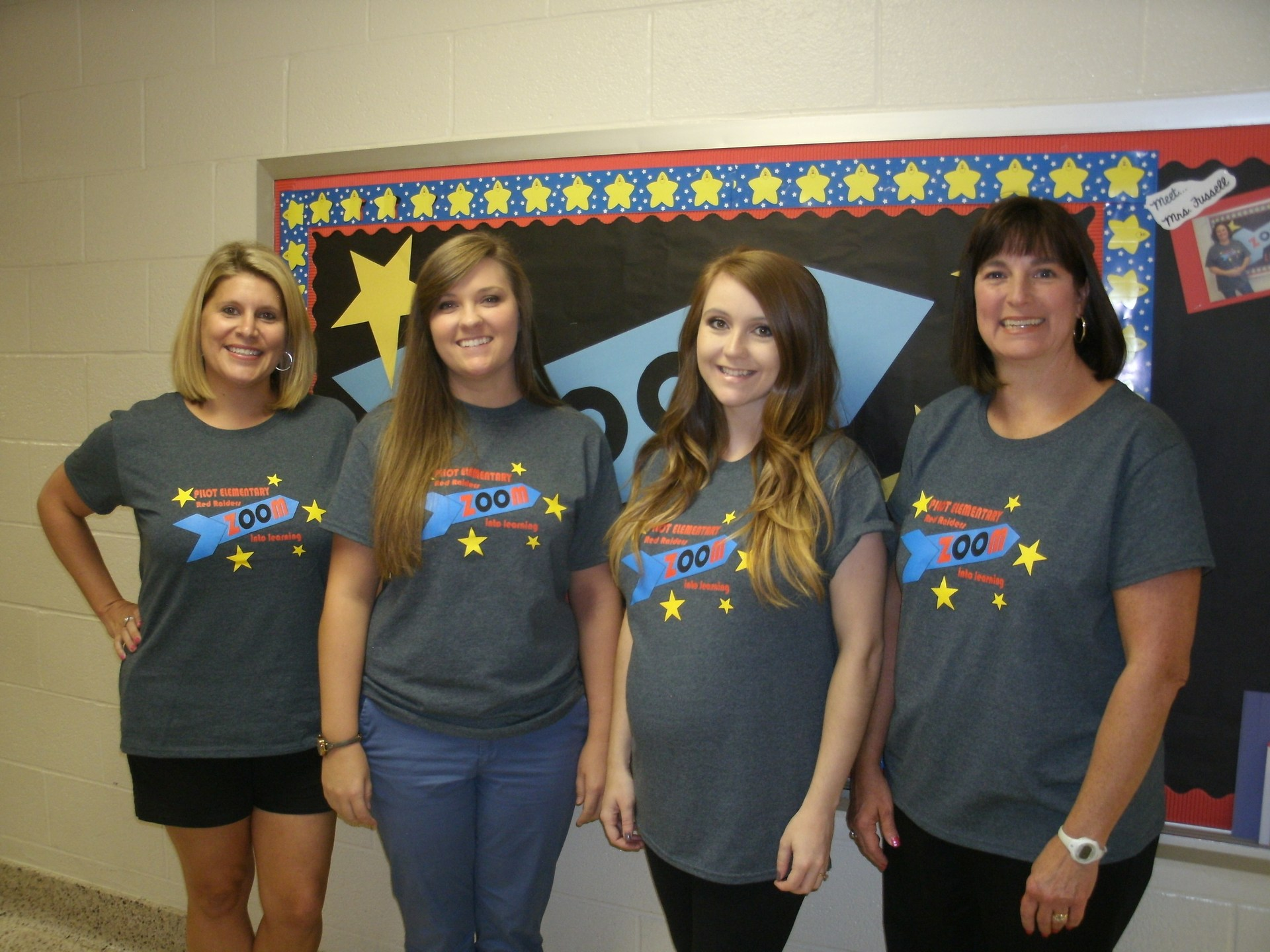 Four second grade teachers are standing in front of a bulletin board.