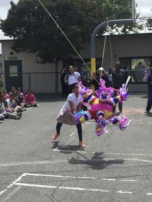 A student attempting to hit a piñata