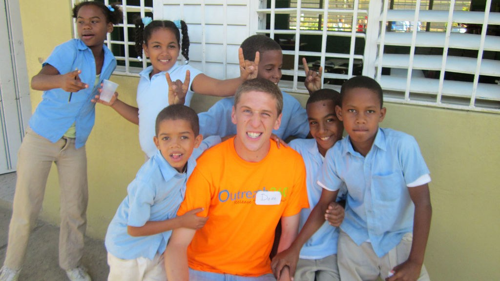 Student posing with local children