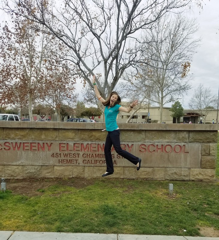 Amber Anderson jumping in front of a McSweeny sign.