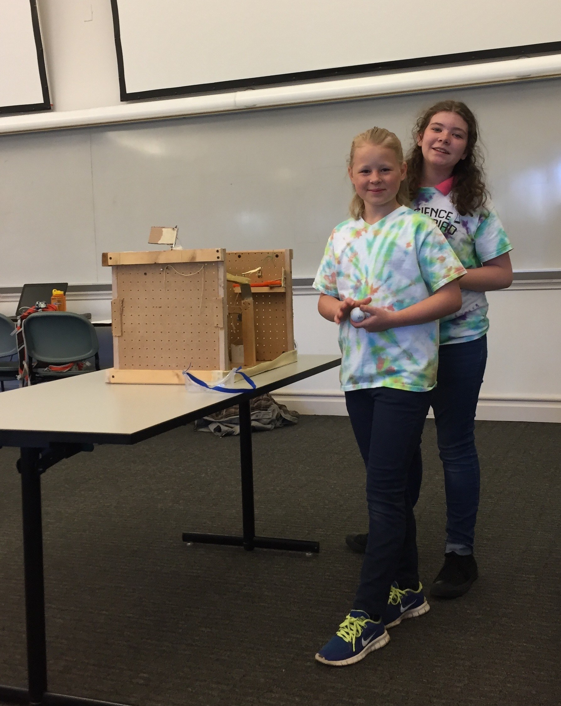 two students standing next to a Science Olympiad project