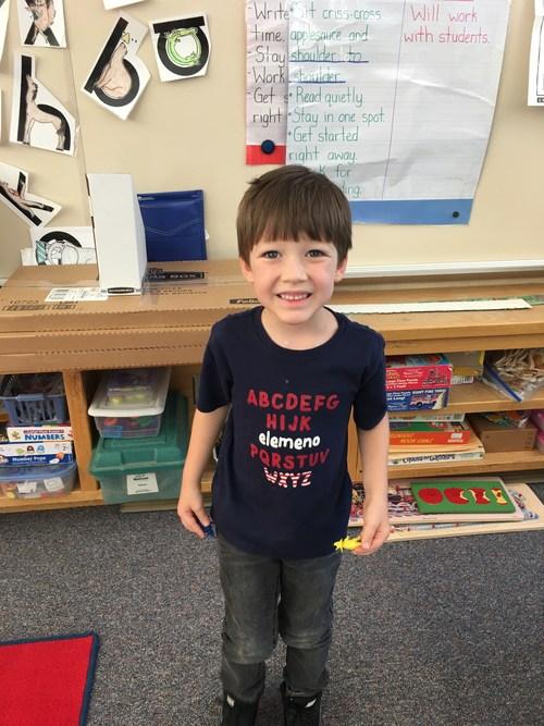 Kindergartner standing in his new classroom.