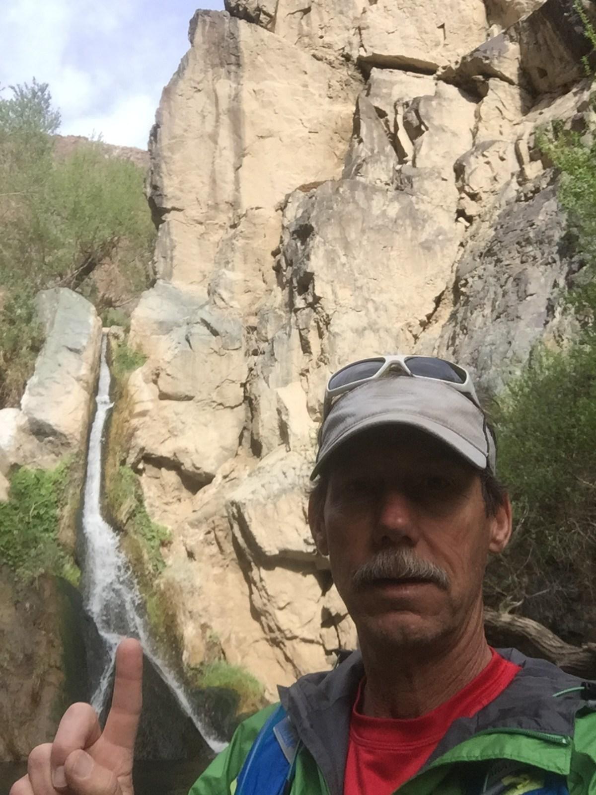 Selfie splitting waterfall with finger.