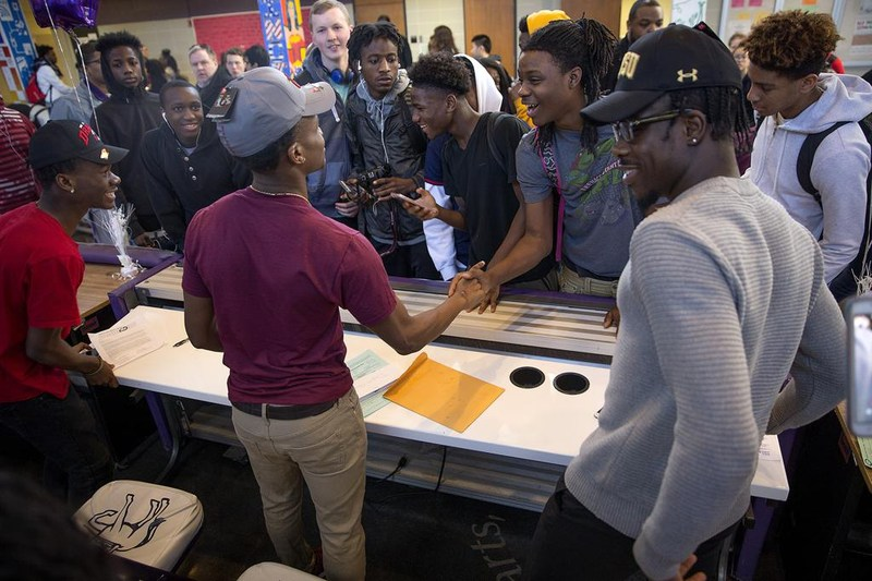 Brooklyn Center football players Junior Kai, left, Dayvia Gbor, center, and Charles Wylie, right were greeted by classmates Wednesday after they signed letters of intent to play in college. Photo: Elizabeth Flores * liz.flores@startribune.com
