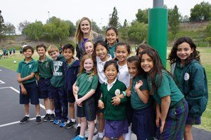 Tara Campbell with St. Francis Student on Playground.JPG