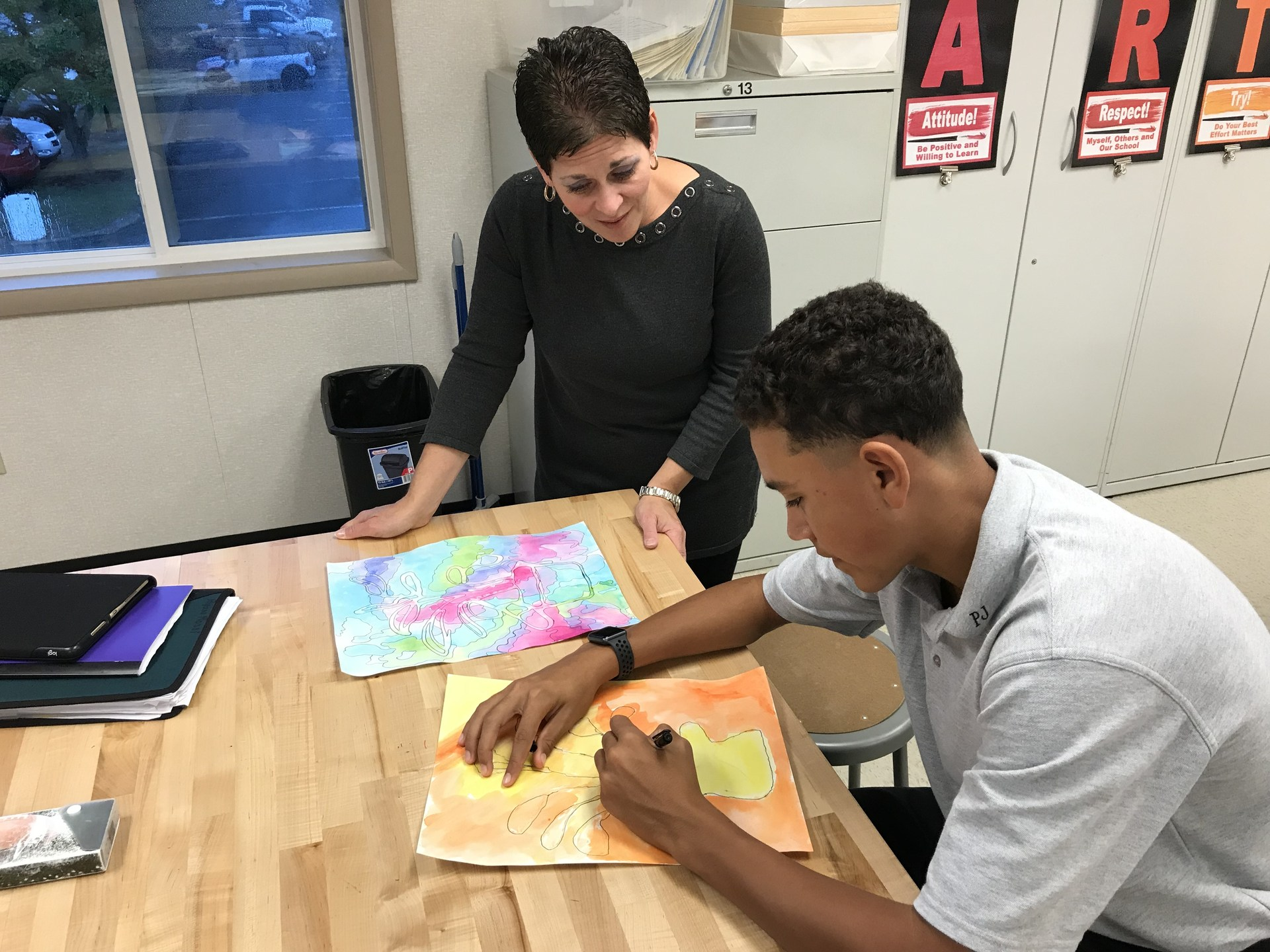 Art teacher helping student with drawing