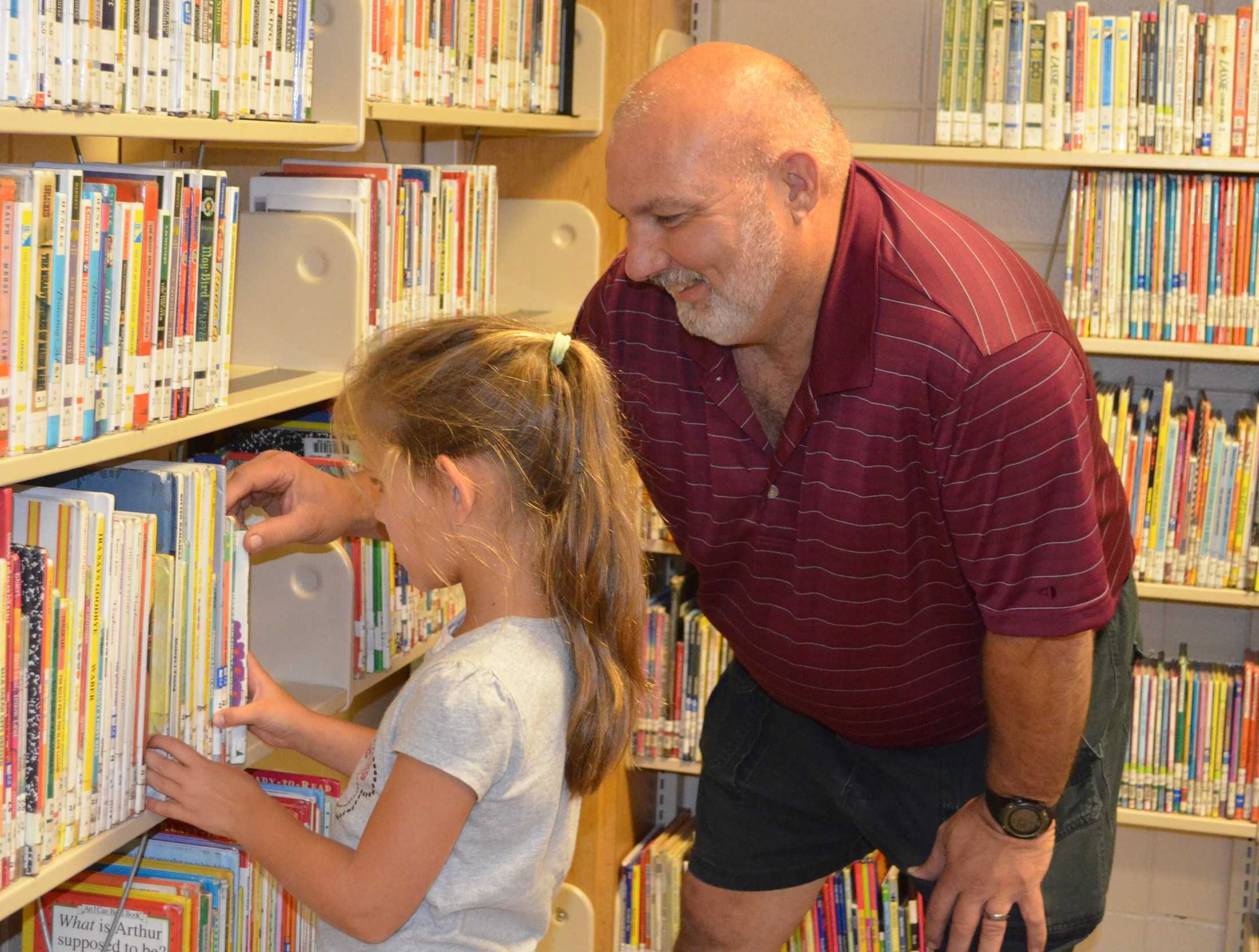 BES student shows grandparent where some of her favorite books are located in the library.