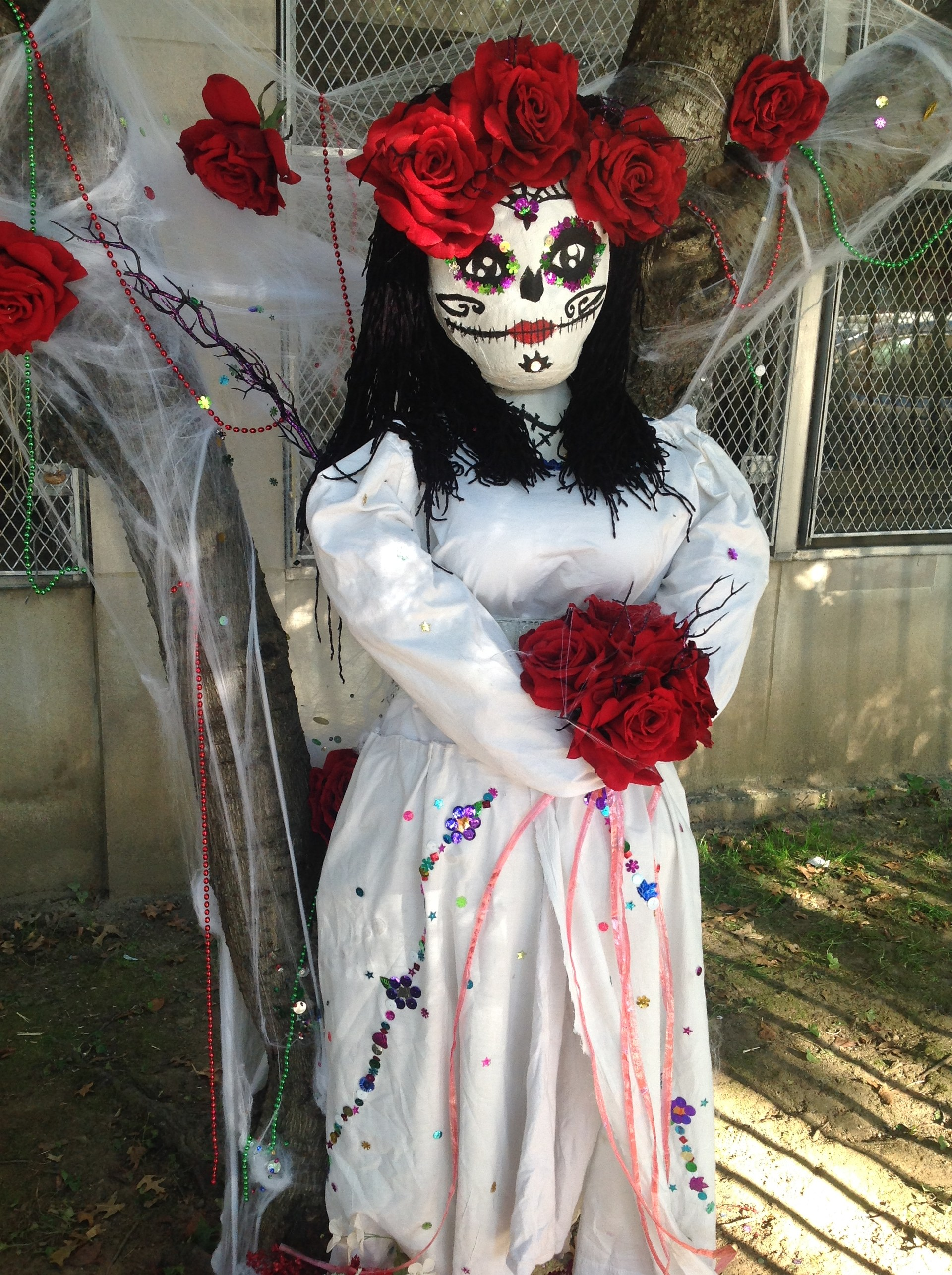 Day of the dead woman scarecrow holding roses.
